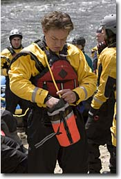 Brian, NW Wholesale Rep, in an NRS Extreme Drysuit, stuffing a throw bag before a spring Lochsa River run.