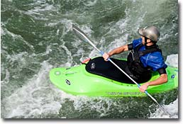 Kurtis, NRS Western Wholesale Account Manager, surfing a Salmon River wave in an NRS Stampede Shorty Paddle Jacket.