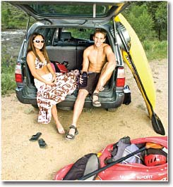 couple of boaters sitting in back of their suv after paddling